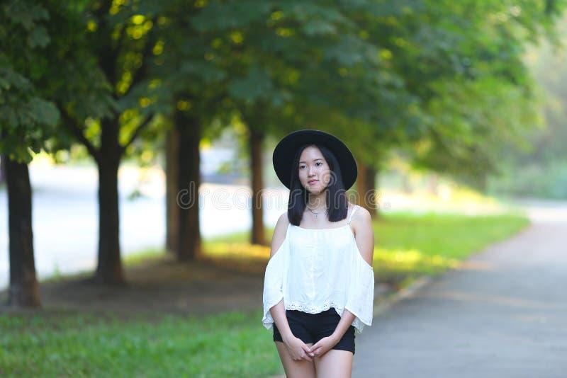 De mooie Aziatische vrouw in een hoed onderzoekt het cameraportret stock afbeelding