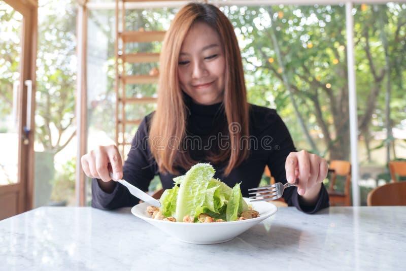 De mooie Aziatische vrouw geniet van etend caesar salade op lijst in het restaurant stock fotografie