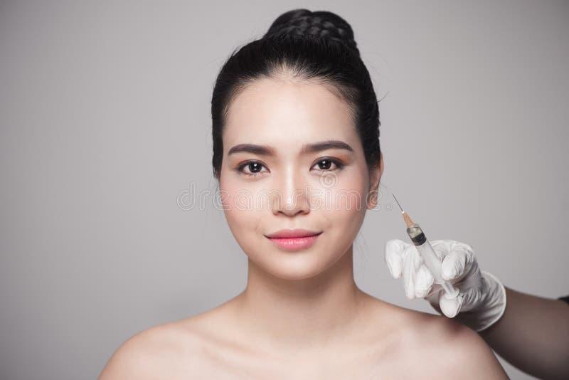De mooie Aziatische vrouw krijgt schoonheids gezichtsinjecties Gezicht het verouderen stock afbeelding