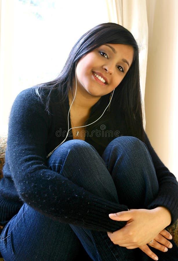 De mooie Aziatische vrouwelijke jeugd die aan haar favoriete muziek binnen luistert