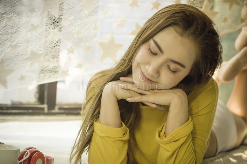 De mooie Aziatische vrouwen met een kop witte koffie en hoofdtelefoons, met ontspannen na ontwaken op bed in de slaapkamer van he stock foto