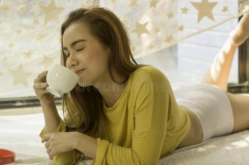 De mooie Aziatische vrouwen met een kop witte koffie en hoofdtelefoons, met ontspannen na ontwaken op bed in de slaapkamer van he stock fotografie