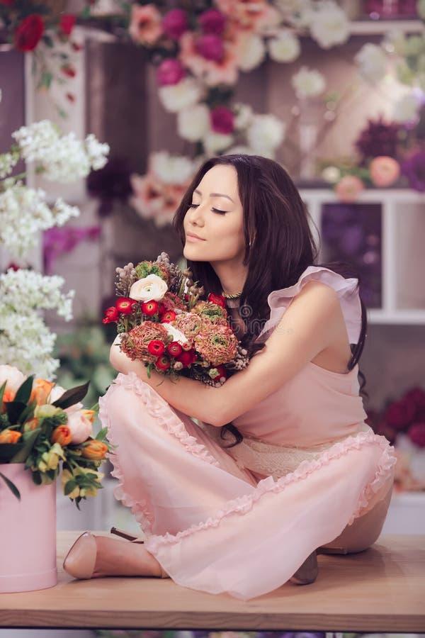 De mooie Aziatische vrouwenbloemist in roze kleding met boeket van bloemen dient binnen bloemopslag in royalty-vrije stock afbeeldingen