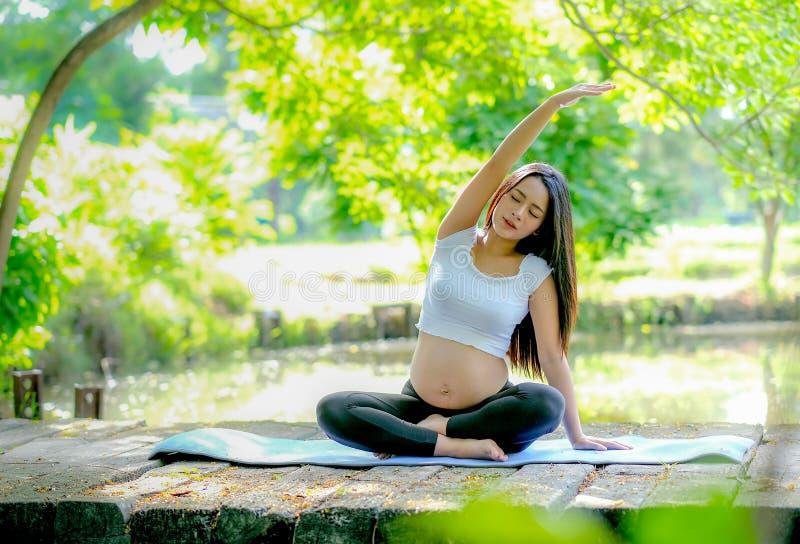 De mooie Aziatische zwangere vrouwenoefening met yogaactie zit langs op houten brug dichtbij de rivier in de tuin met ochtendlich stock afbeeldingen