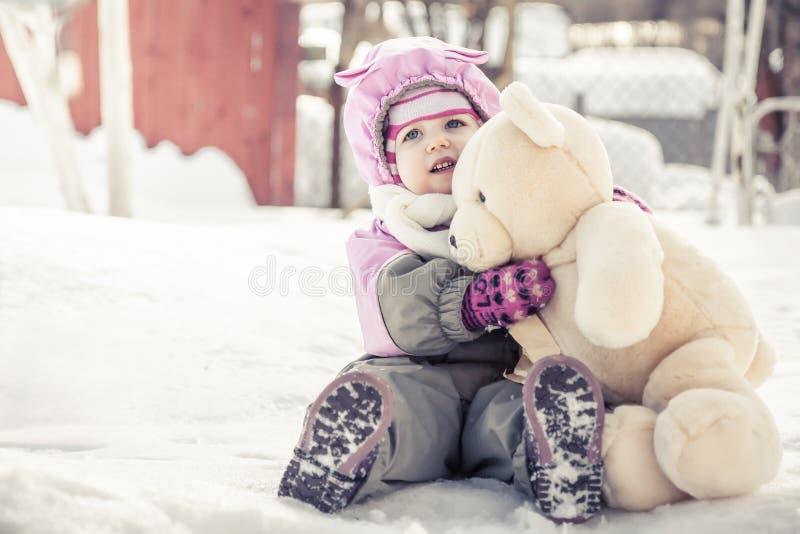 De mooie baby die stuk speelgoed pluche omhelzen draagt zittend op sneeuw in park in koude zonnige de winterdag tijdens de winter stock afbeeldingen