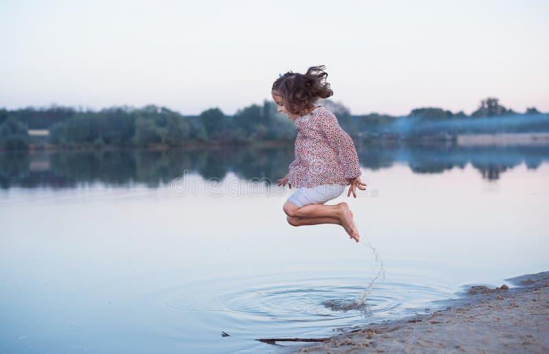 De mooie baby met krullend haar springt cheerfully op de bank van het meer Actieve de lentegang in openlucht royalty-vrije stock foto