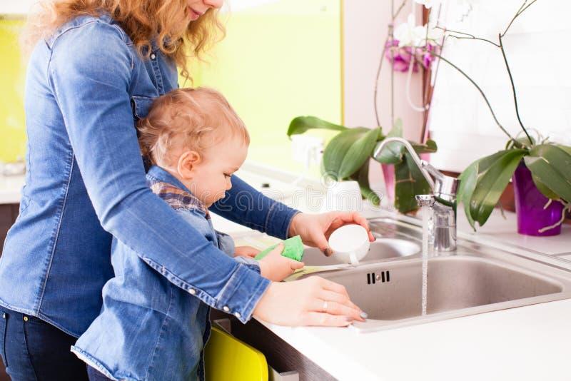 De mooie baby wil zijn moeder helpen om de schotels te wassen royalty-vrije stock fotografie
