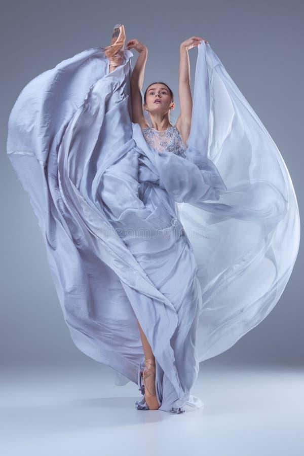 De mooie ballerina die in blauwe lange kleding dansen royalty-vrije stock fotografie