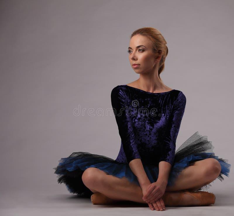 De mooie ballerina met perfect lichaam in blauwe tutu zit in studio Klassiek ballet stock afbeeldingen