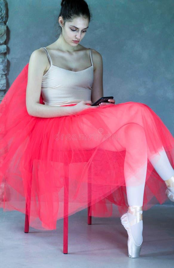 De mooie balletdanserzitting ontspant binnen met telefoon stock afbeelding