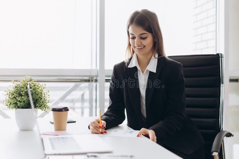 De mooie bedrijfsdame bekijkt laptop en glimlacht terwijl het werken in bureau Geconcentreerd op het werk stock foto