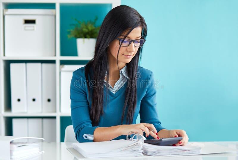 De mooie bedrijfsvrouw berekent belasting royalty-vrije stock foto's