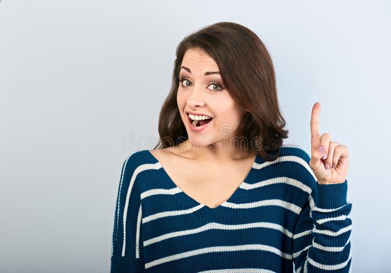 De mooie bedrijfsvrouw die het teken van het vingeridee tonen en omhoog op wijnoogst kijken stemde achtergrond met lege exemplaar stock foto
