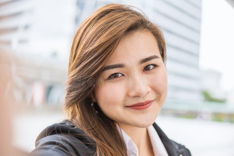 De mooie bedrijfsvrouw neemt een zelfportret met haar slimme buiten telefoon royalty-vrije stock foto