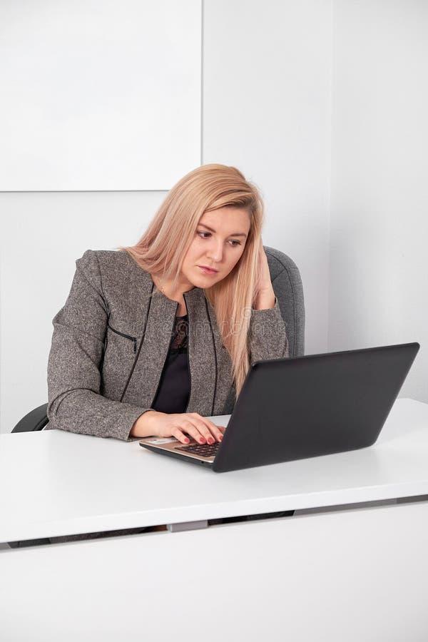 De mooie bedrijfsvrouw werkt achter laptop op kantoor royalty-vrije stock afbeeldingen