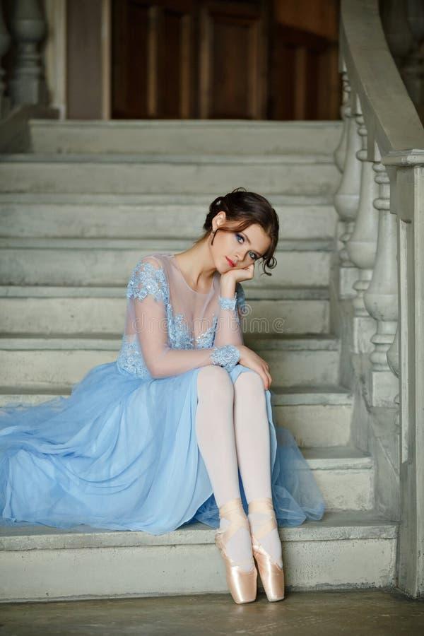 De mooie bevallige meisjesballerina in een blauwe kleding en pointe is stock afbeelding