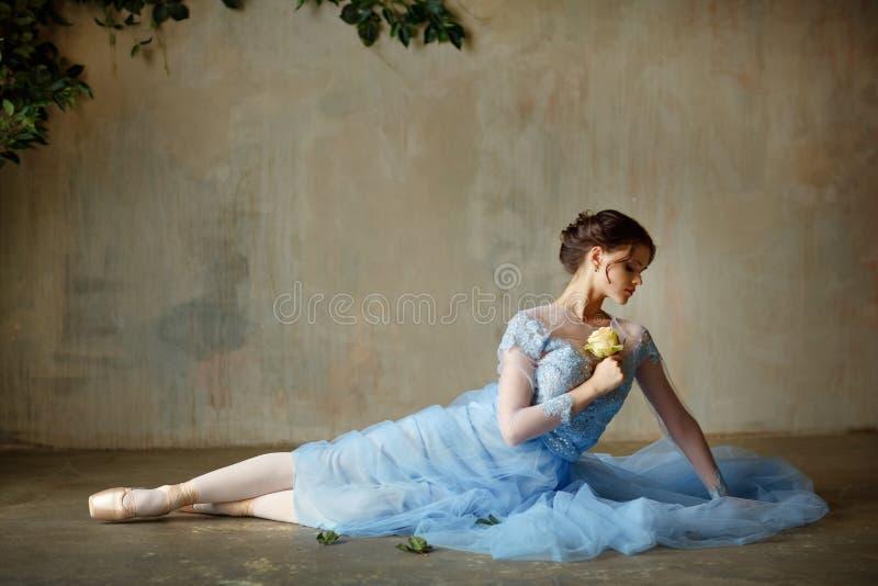 De mooie bevallige meisjesballerina in een blauwe kleding en pointe zit royalty-vrije stock foto