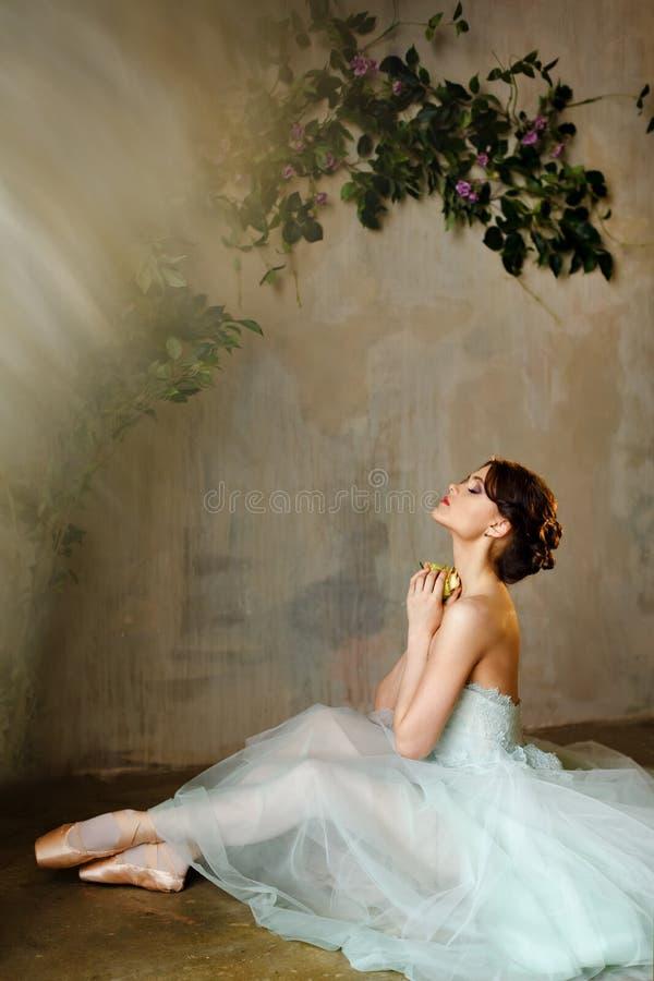 De mooie bevallige meisjesballerina in een luchtkleding en pointe zit royalty-vrije stock afbeeldingen