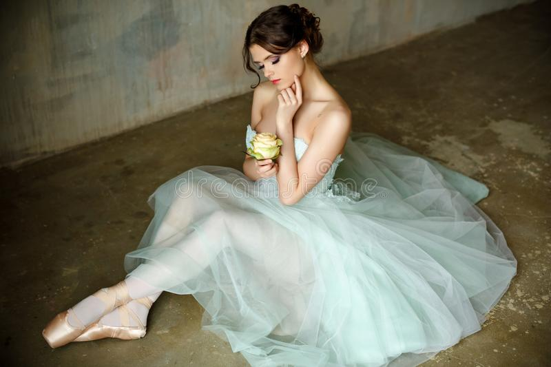 De mooie bevallige meisjesballerina in een luchtkleding en pointe zit stock foto