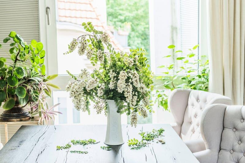 De mooie bloemenbos met bloesemacacia vertakt zich in witte vaas op lijst in woonkamer bij venster Binnenlandse ontwerp en ideeën stock fotografie