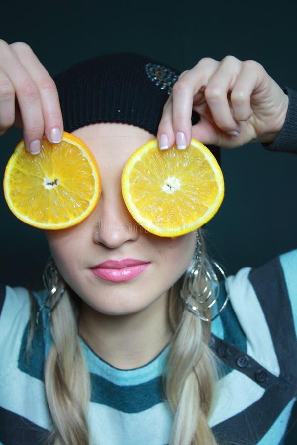 De mooie blonde houdt oranje stock foto