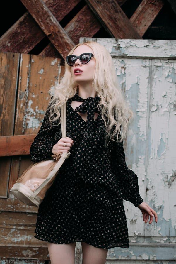 De mooie blonde jonge vrouw zonnebril dragen, de zwarte bovenkant en het potlood die begrenzen, hoed en handtas, die zich op de s royalty-vrije stock foto