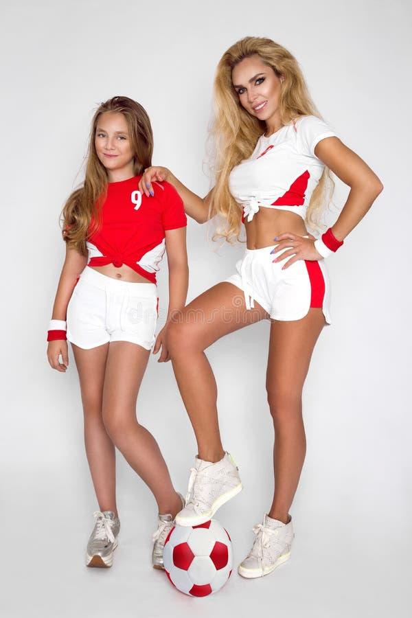 De mooie blonde meisjes, de moeder en de dochter kleedden zich in sporten stock fotografie
