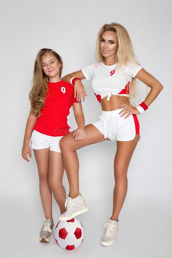 De mooie, blonde meisjes, de moeder en de dochter kleedden zich in sporten c stock afbeeldingen