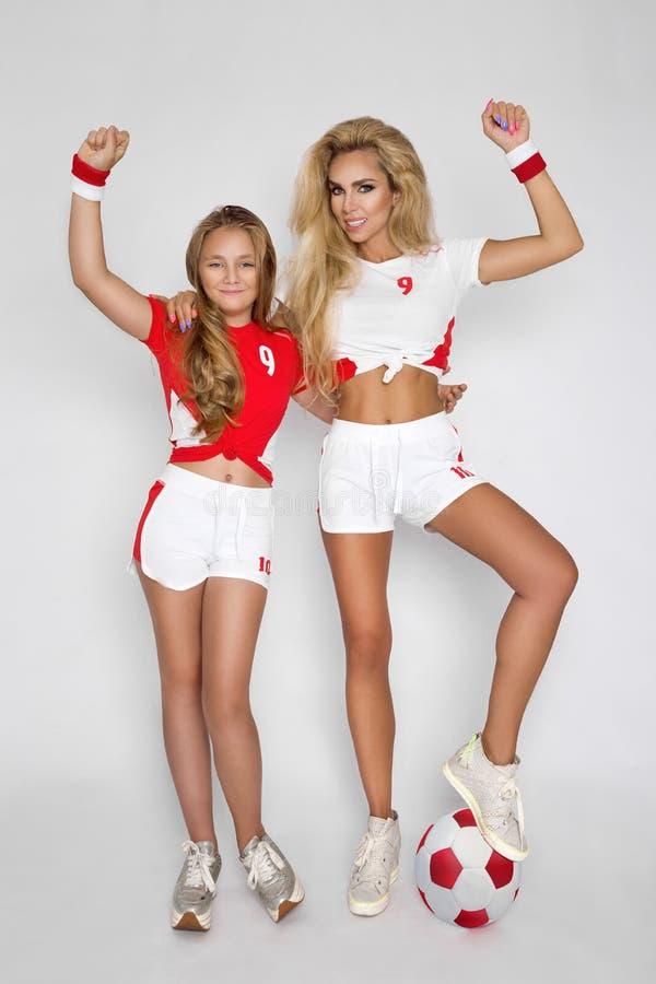 De mooie, blonde meisjes, de moeder en de dochter kleedden zich in sporten c royalty-vrije stock foto