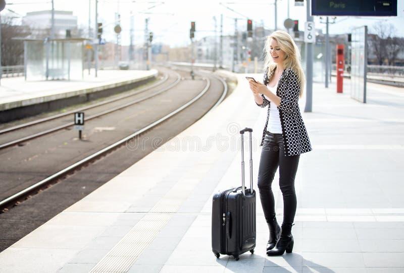 De mooie blonde vrouw leest sms bij het station stock foto's