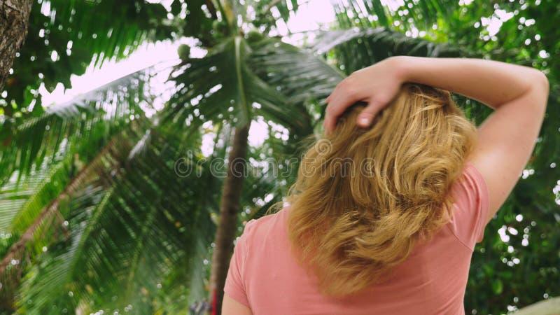 De mooie blonde vrouw raakt haar haar in aard Achter mening Het Concept van de haarbehandeling royalty-vrije stock afbeelding