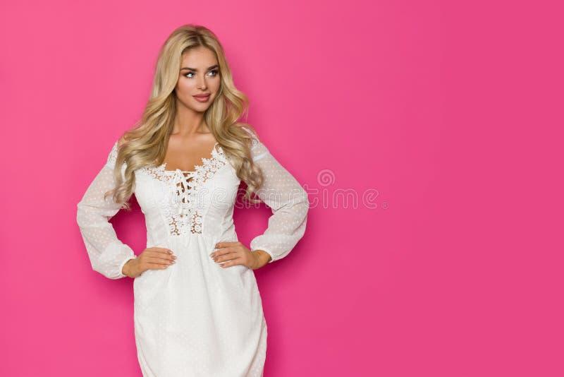 De mooie Blonde Vrouw in Witte Kleding is Holdingshand op Heup en weg het Kijken royalty-vrije stock foto's