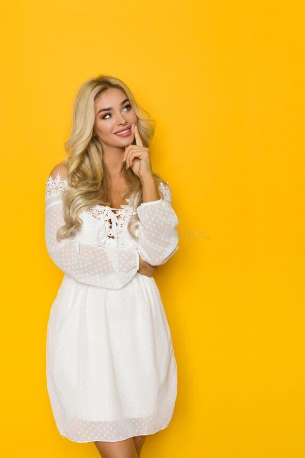 De mooie Blonde Vrouw in Witte Kleding is Holdingshand op Omhooggaand en Kin die, die kijken denken stock afbeeldingen