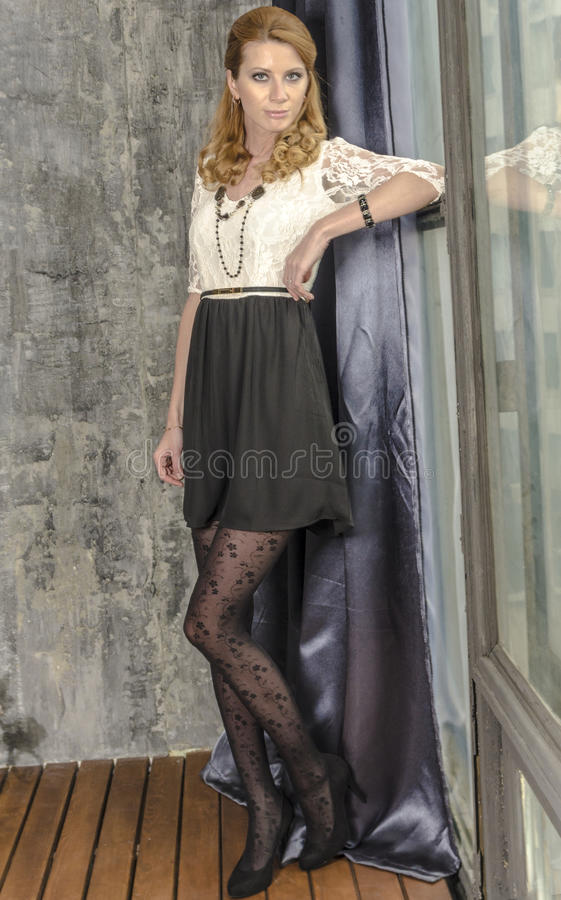De mooie blondevrouw in een kleding zit in een antieke ruimte door het venster stock afbeelding