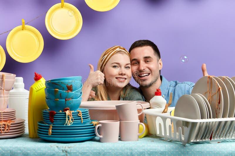 De mooie blondevrouw en de donker-haired echtgenoot die van hun tijd in genieten kicthen stock afbeelding