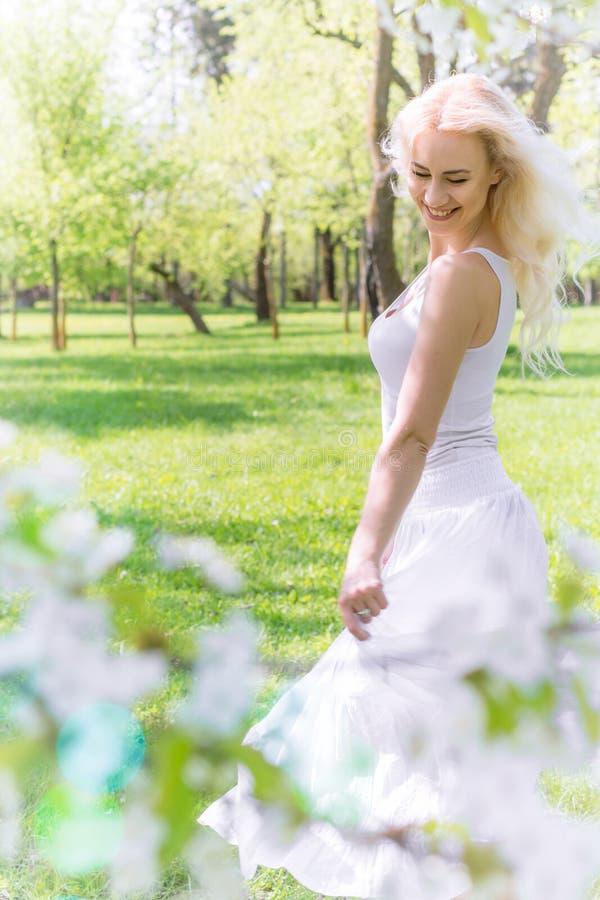 De mooie Blondevrouw geniet van in de Bloeiende Tuin stock foto