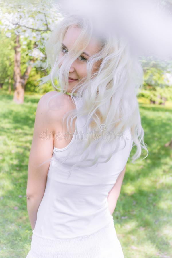 De mooie Blondevrouw geniet van in de Bloeiende Tuin royalty-vrije stock foto's