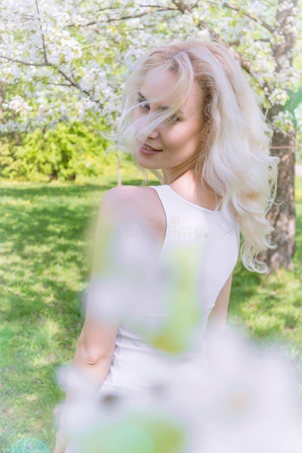 De mooie Blondevrouw geniet van in de Bloeiende Tuin royalty-vrije stock foto