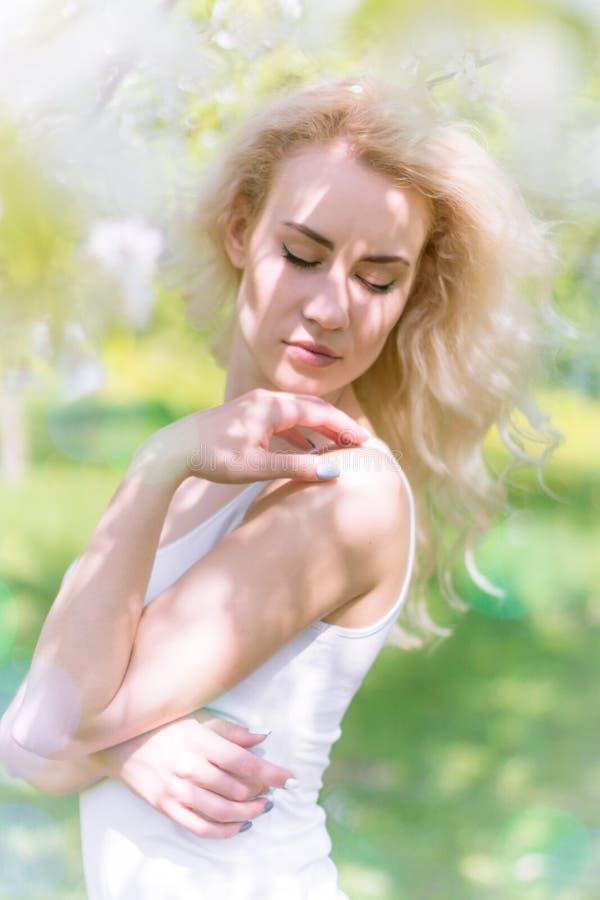 De mooie Blondevrouw geniet van in de Bloeiende Tuin stock fotografie