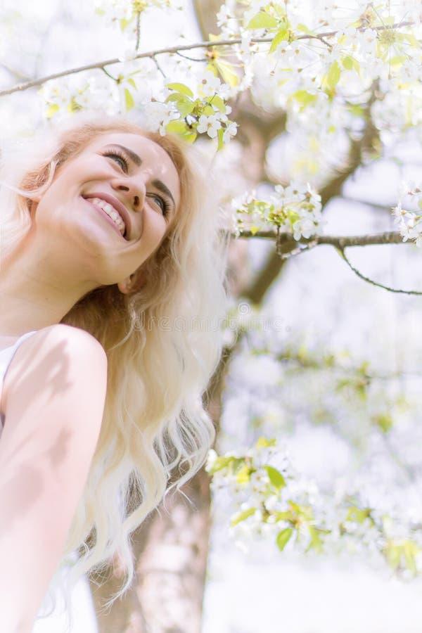 De mooie Blondevrouw geniet van in de Bloeiende Tuin stock foto's
