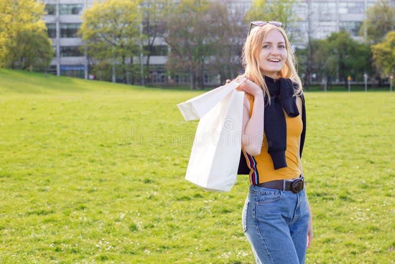 De mooie blondevrouw geniet van het winkelen Consumentisme, het winkelen spot omhoog, levensstijlconcept stock foto