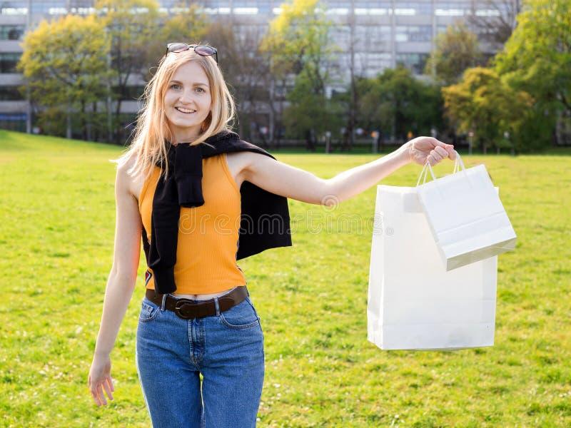 De mooie blondevrouw geniet van het winkelen Consumentisme, het winkelen spot omhoog, levensstijlconcept stock afbeeldingen