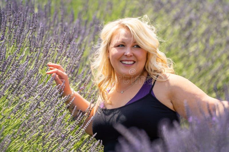 De mooie blondevrouw glimlacht weg en kijkt aangezien zij op een gebied van lavendel zit Genomen in MT kap Oregon stock foto's