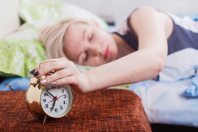 de mooie blondevrouw ligt op het bed met haar die ogen en draaien van de wekker met haar hand worden gesloten royalty-vrije stock foto's