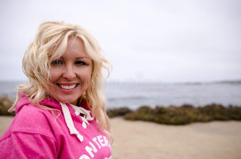 De mooie blondevrouw met strandgolven en touseled haartribunes en stelt binnen op een winderig strand langs de Vreedzame Kustweg stock afbeeldingen