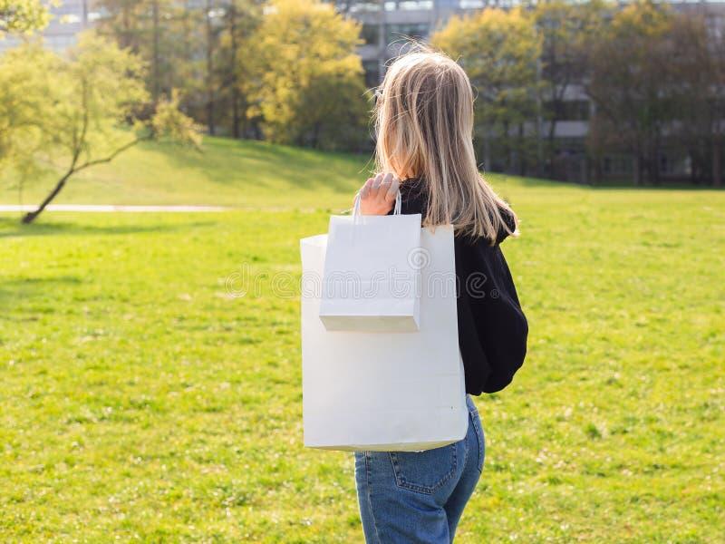 De mooie blondevrouw met zonnebril geniet van het winkelen Consumentisme, het winkelen spot omhoog, levensstijlconcept stock foto