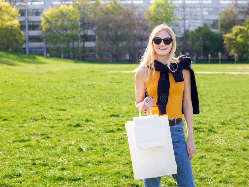 De mooie blondevrouw met zonnebril geniet van het winkelen Consumentisme, het winkelen spot omhoog, levensstijlconcept stock afbeelding