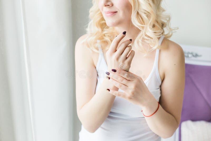 De mooie blondevrouw past room op huid toe en wrijft haar handen en schouder Huid en lichaamsverzorging door te bevochtigen stock fotografie