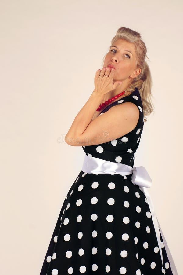 De mooie blondevrouw in pinupstijl kleedde zich rond in de draaien van een stipkleding en blaast een kus, witte achtergrond stock fotografie