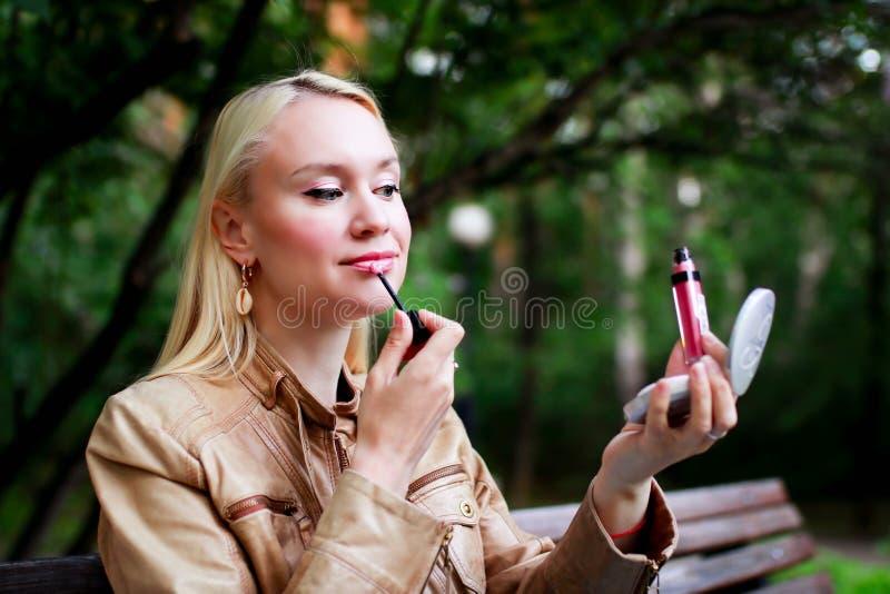 De mooie blondevrouw schildert in openlucht haar lippen Het verbeteren maakt omhoog royalty-vrije stock afbeelding